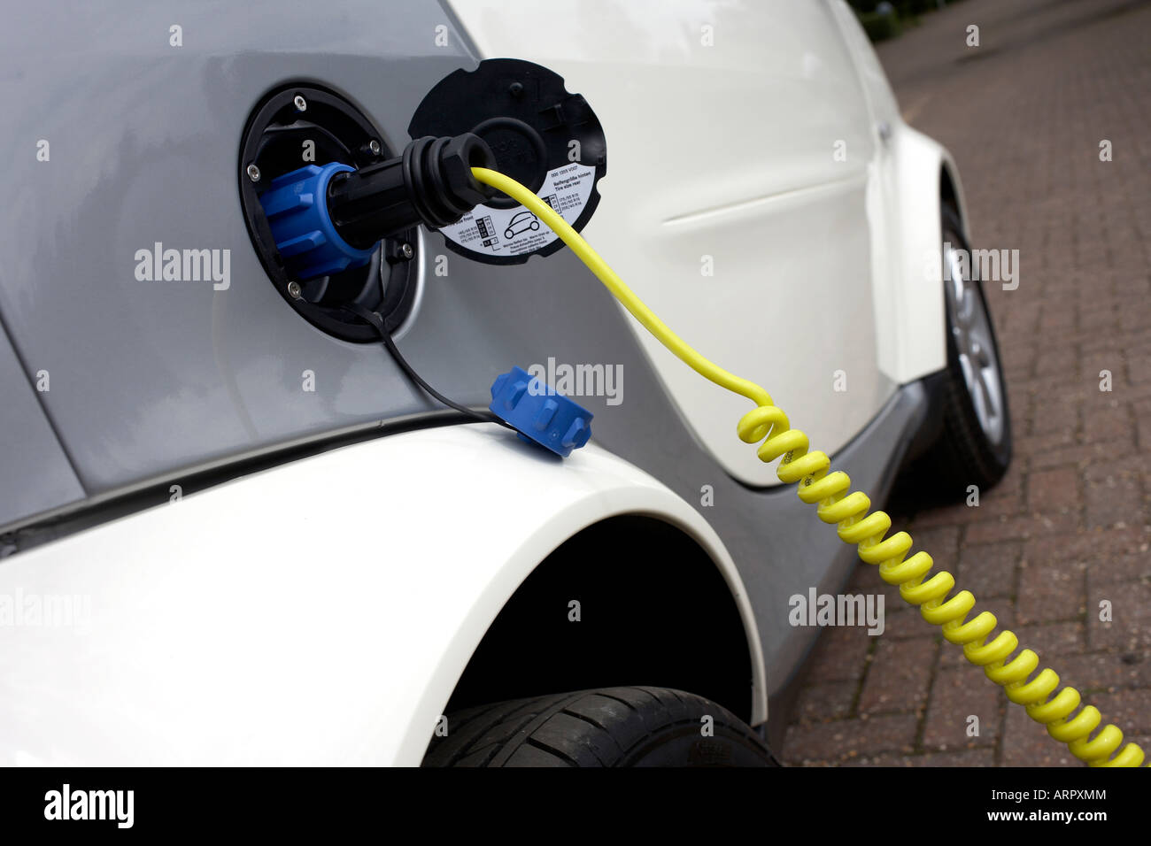Re-charging an MHD Smart Car from mains electricity which powers its engine, an environmentally-green alternative Stock Photo