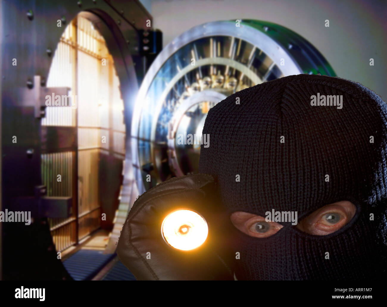 bank robber with ski mask and flashlight in bank vault - Stock Image