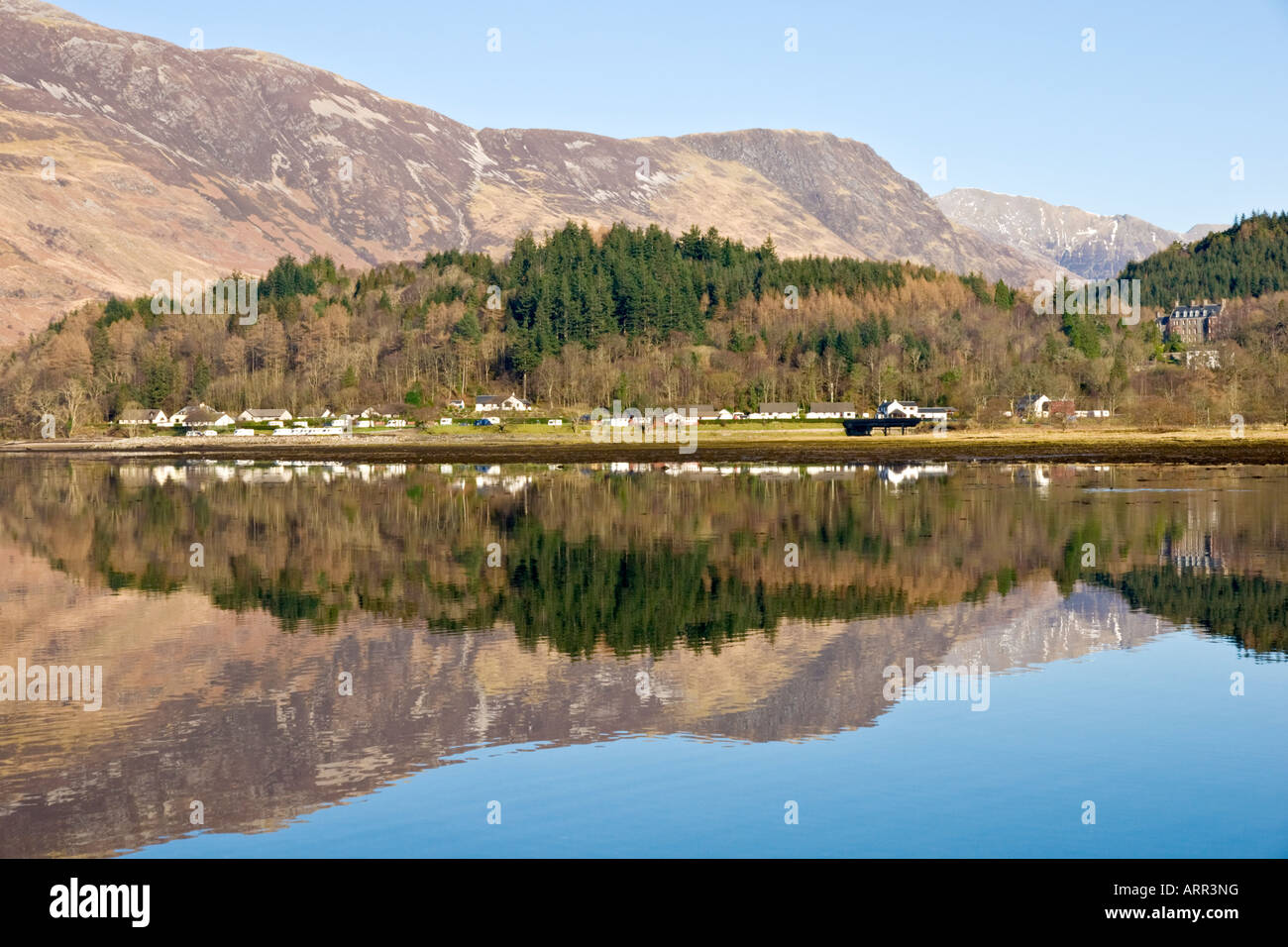 North end of Glencoe village with houses and mountains reflected in Loch leven West Highlands Scotland - Stock Image