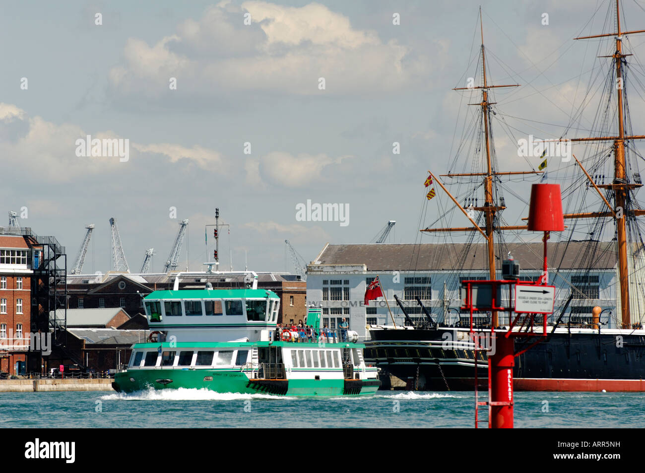 the gosport ferry making its way across portsmouth harbour with hms wario and victory in the background at the historic - Stock Image