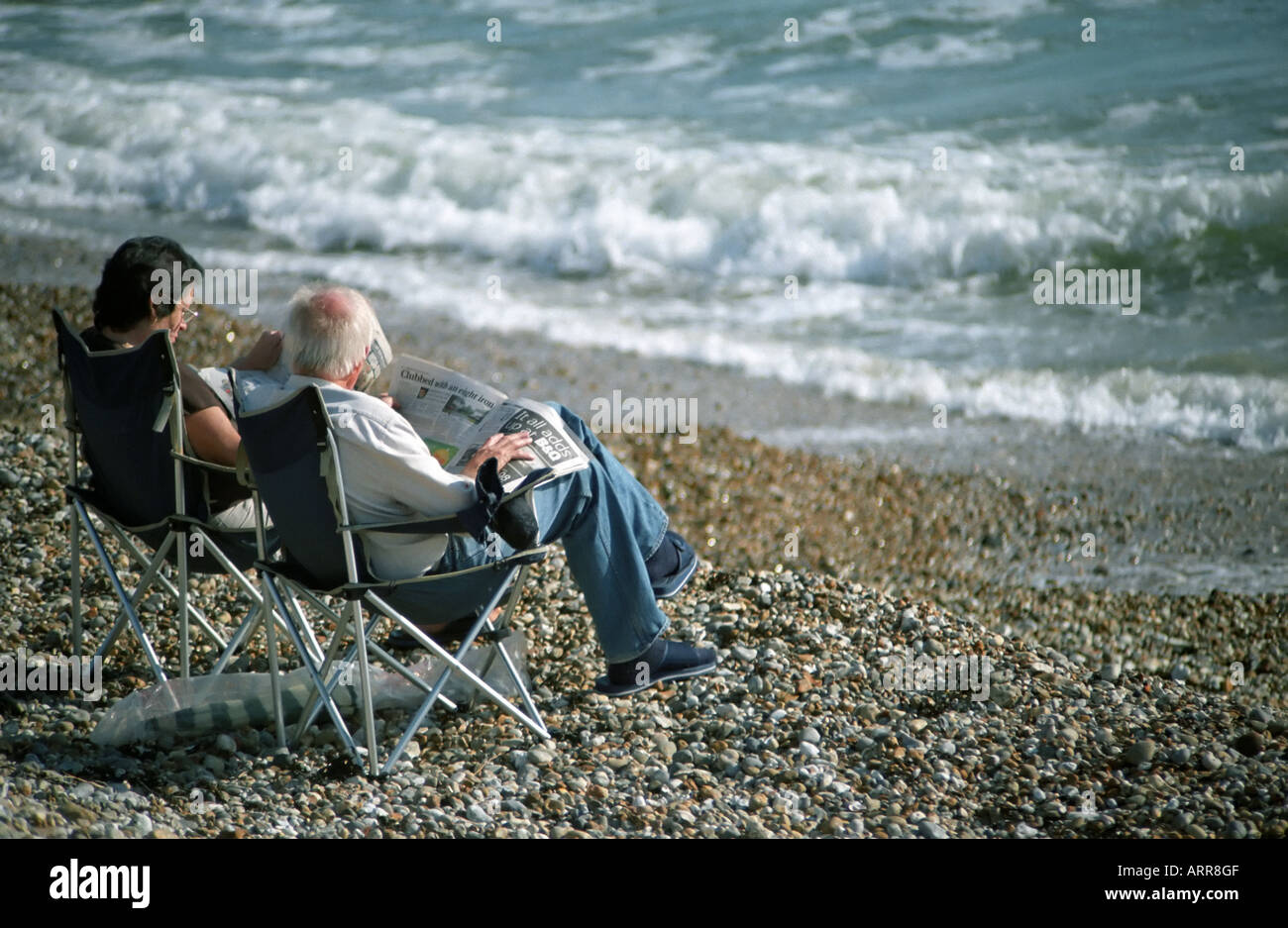 An older couple sitting in deckchairs reading newspapers on a shingle beach by the sea at East Wittering in Sussex Stock Photo