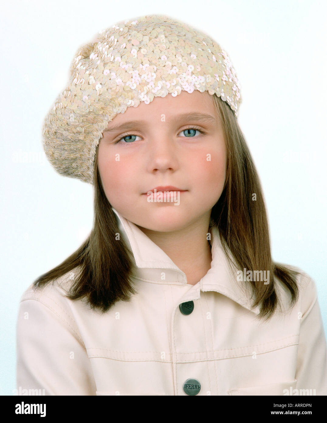 A young girl wearing makeup in a sequin beret - Stock Image