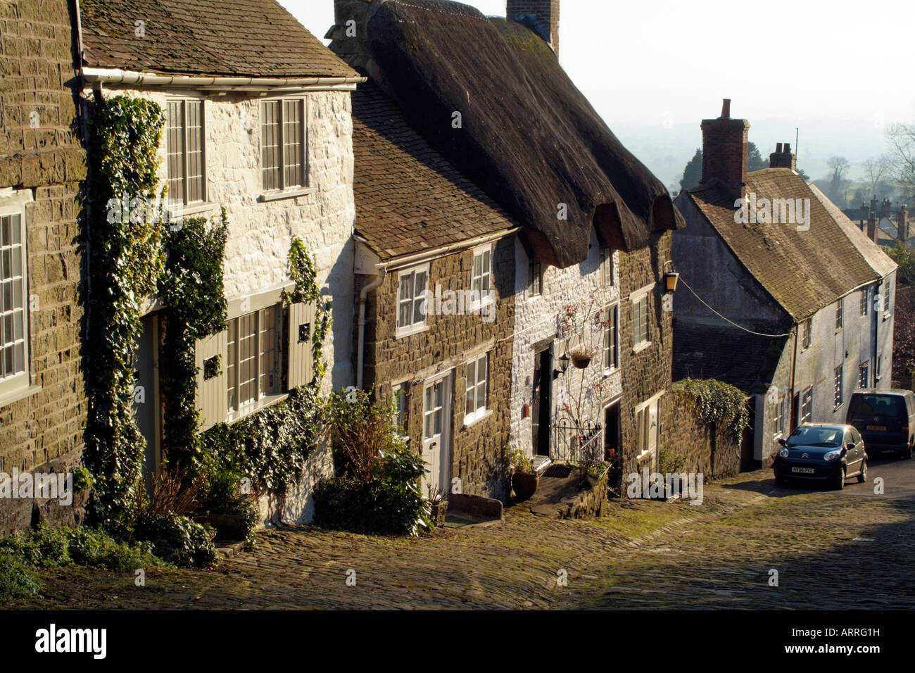 Gold Hill made famous by Hovis Advertisement in Shaftesbury Dorset England Edge of Town Housing Wintertime landscape - Stock Image