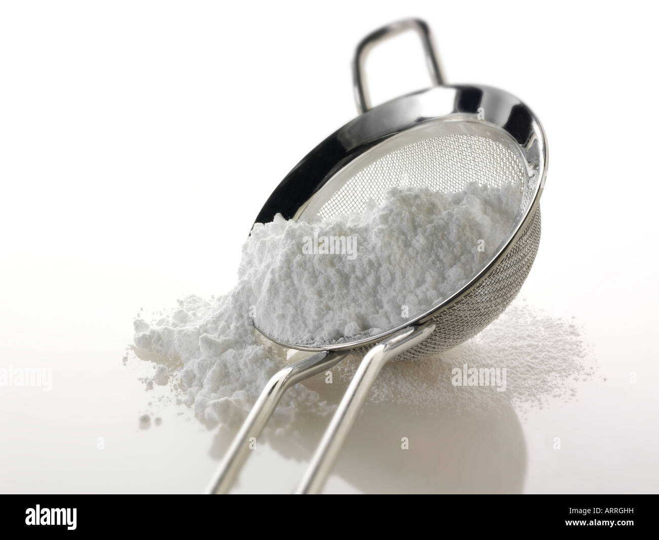 Icing sugar on a sieve against a white background - Stock Image