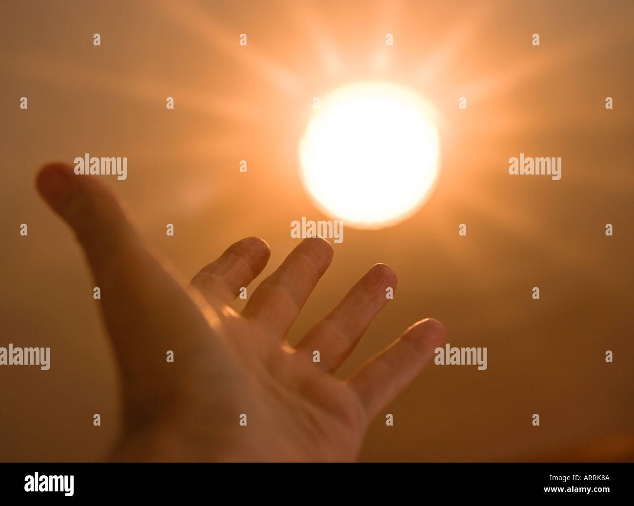 Hand reaching for sun - Stock Image