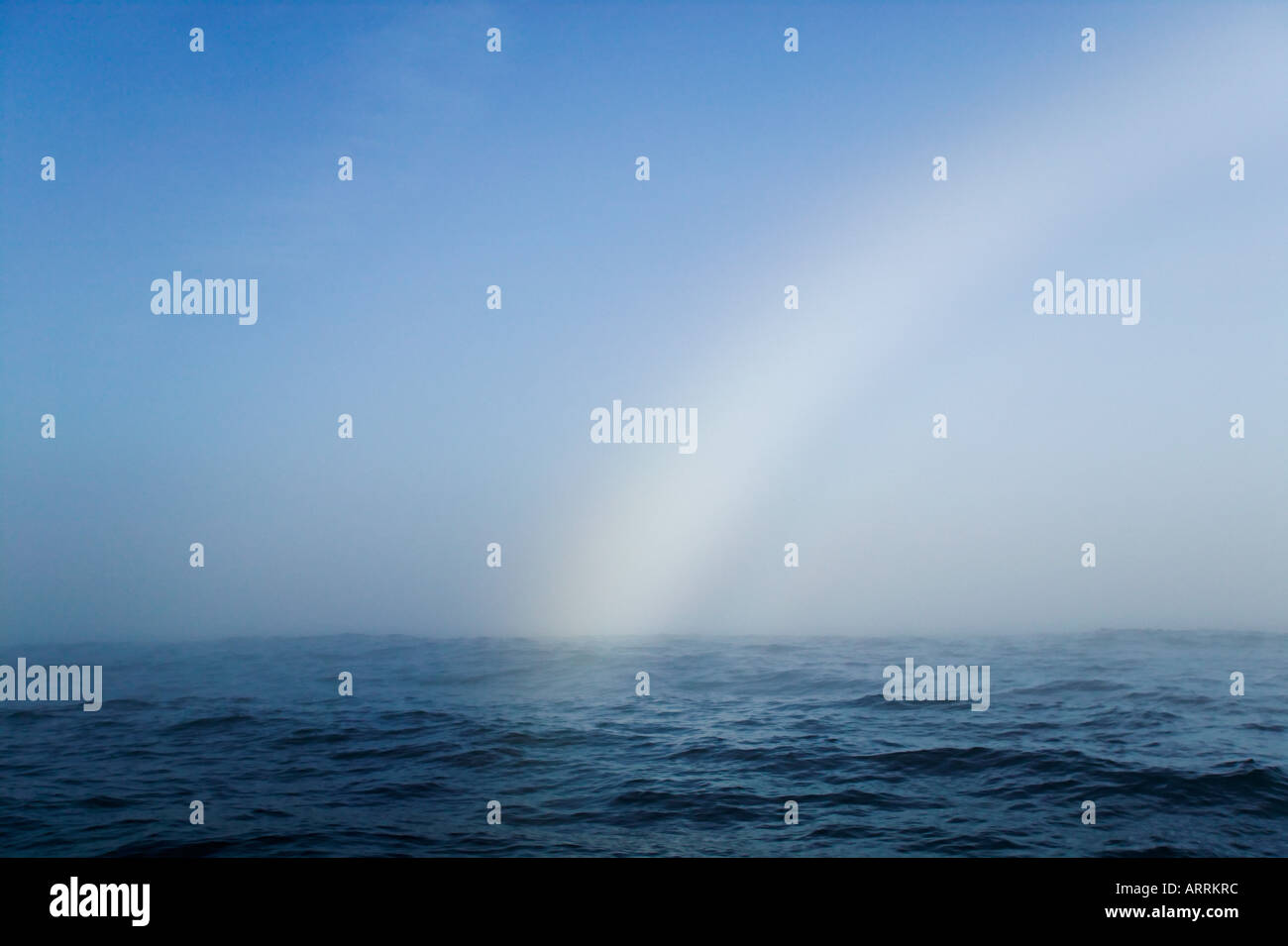 Rainbow fading over the ocean - Stock Image