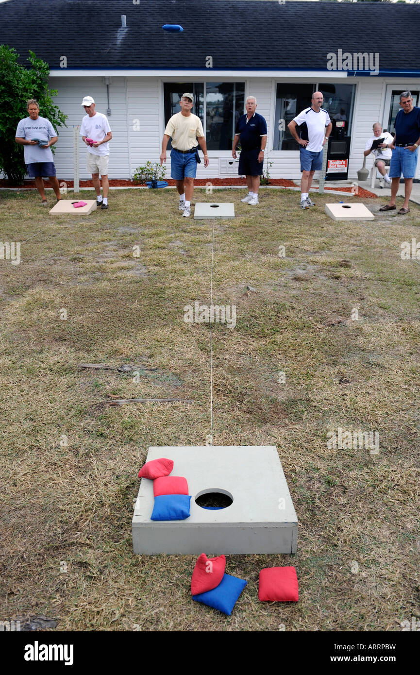 Senior retired citizens play game of bean bag toss in a recreational vechile camping park in Bonita Springs Florida - Stock Image
