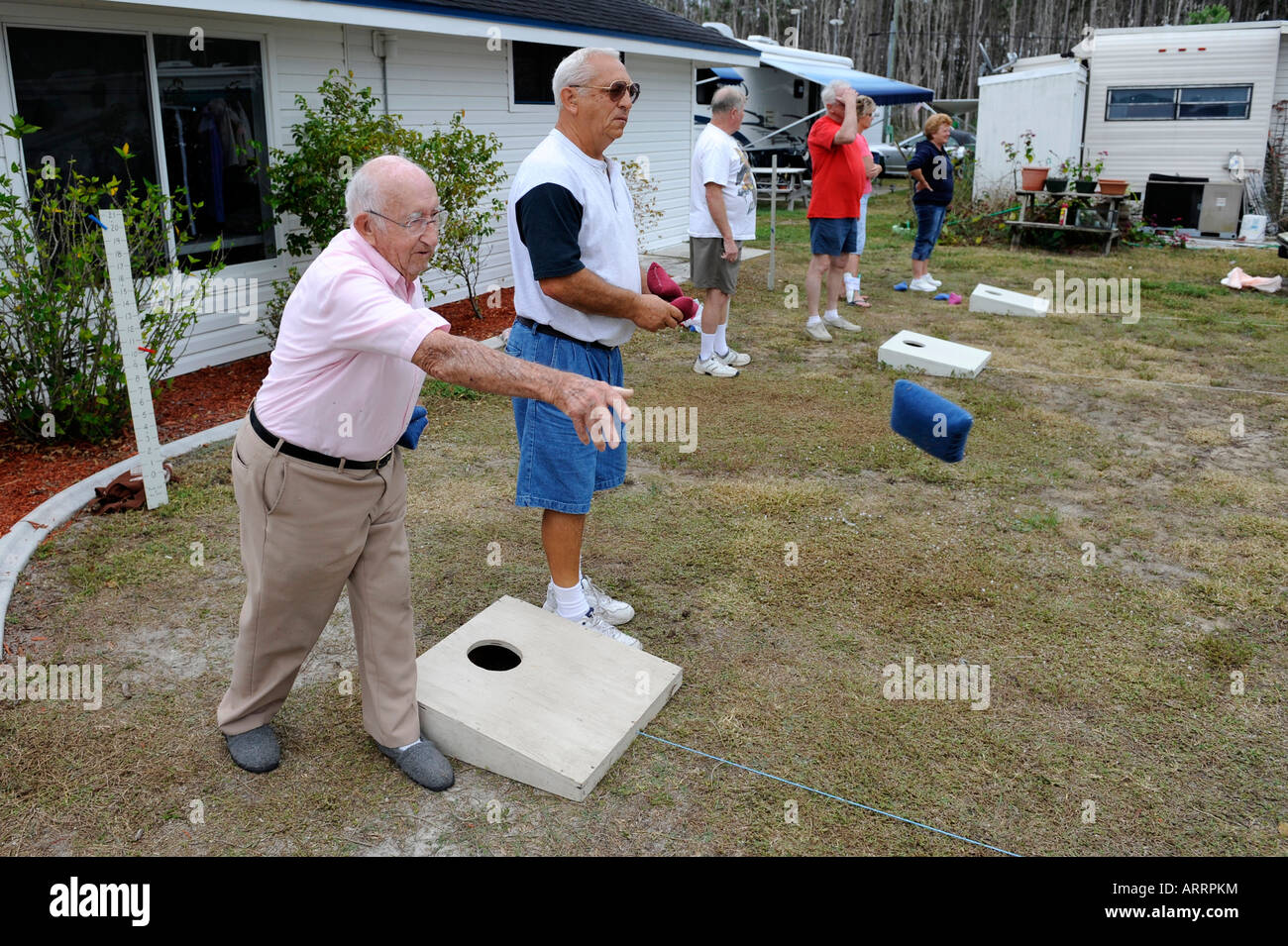 93 year old Senior retired citizen plays game of bean bag toss in a recreational vehicle camping park in Bonita - Stock Image