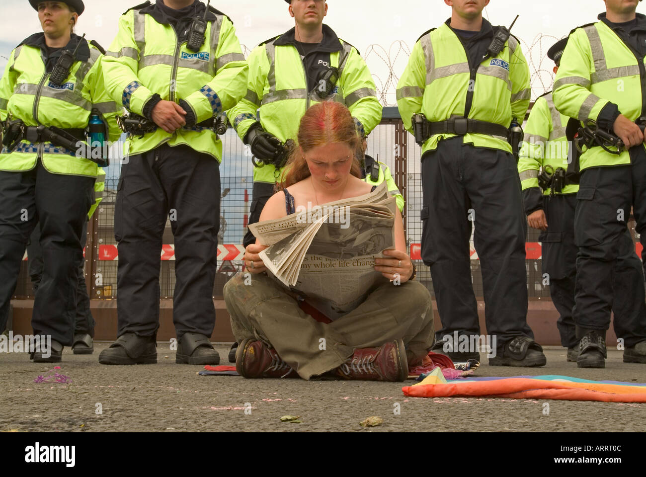 Lone protester reads a newspaper in front of police line at Faslane nuclear base. - Stock Image