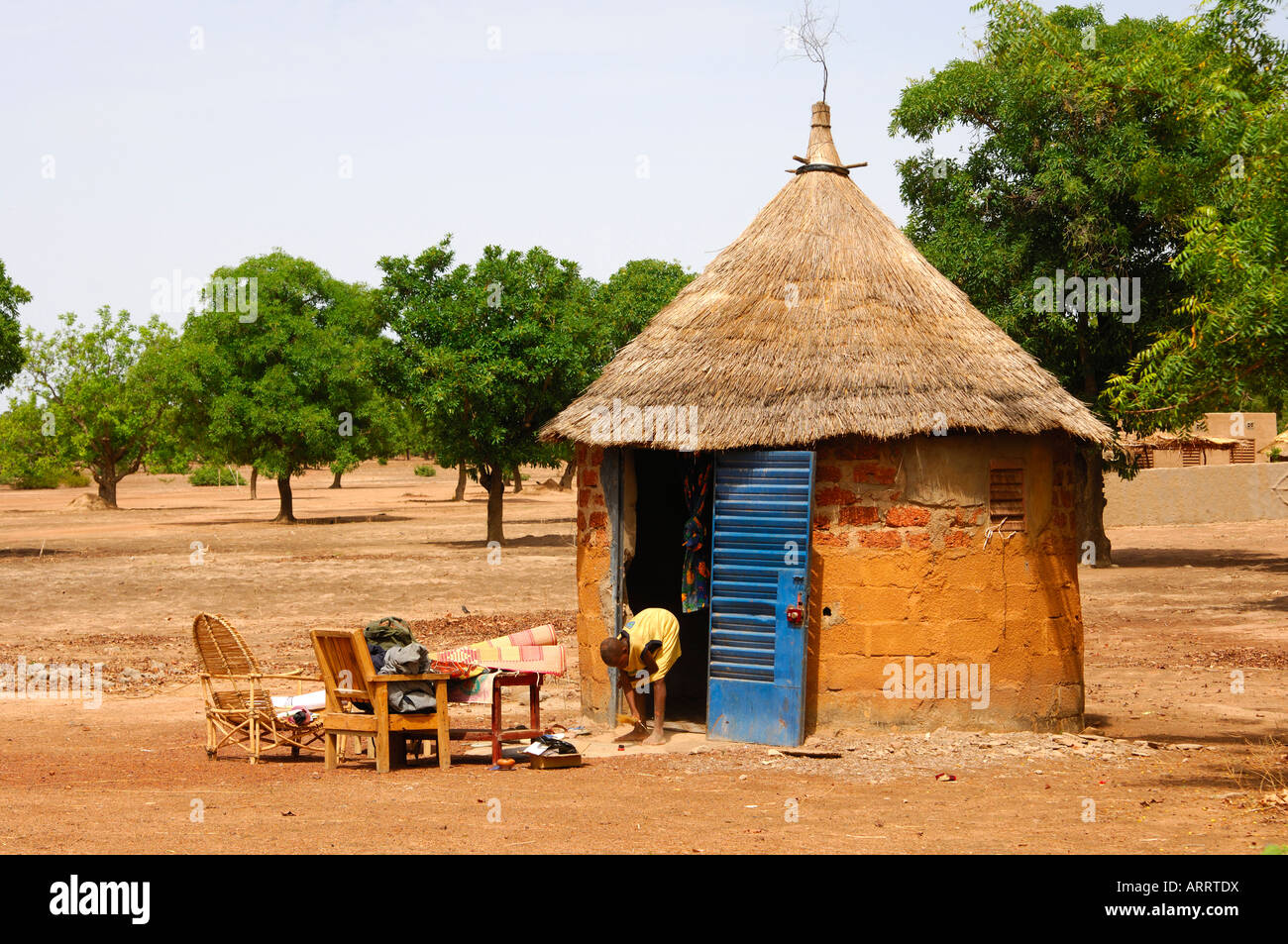 Boy Cleaning An African Round Hut With Thatched Roof