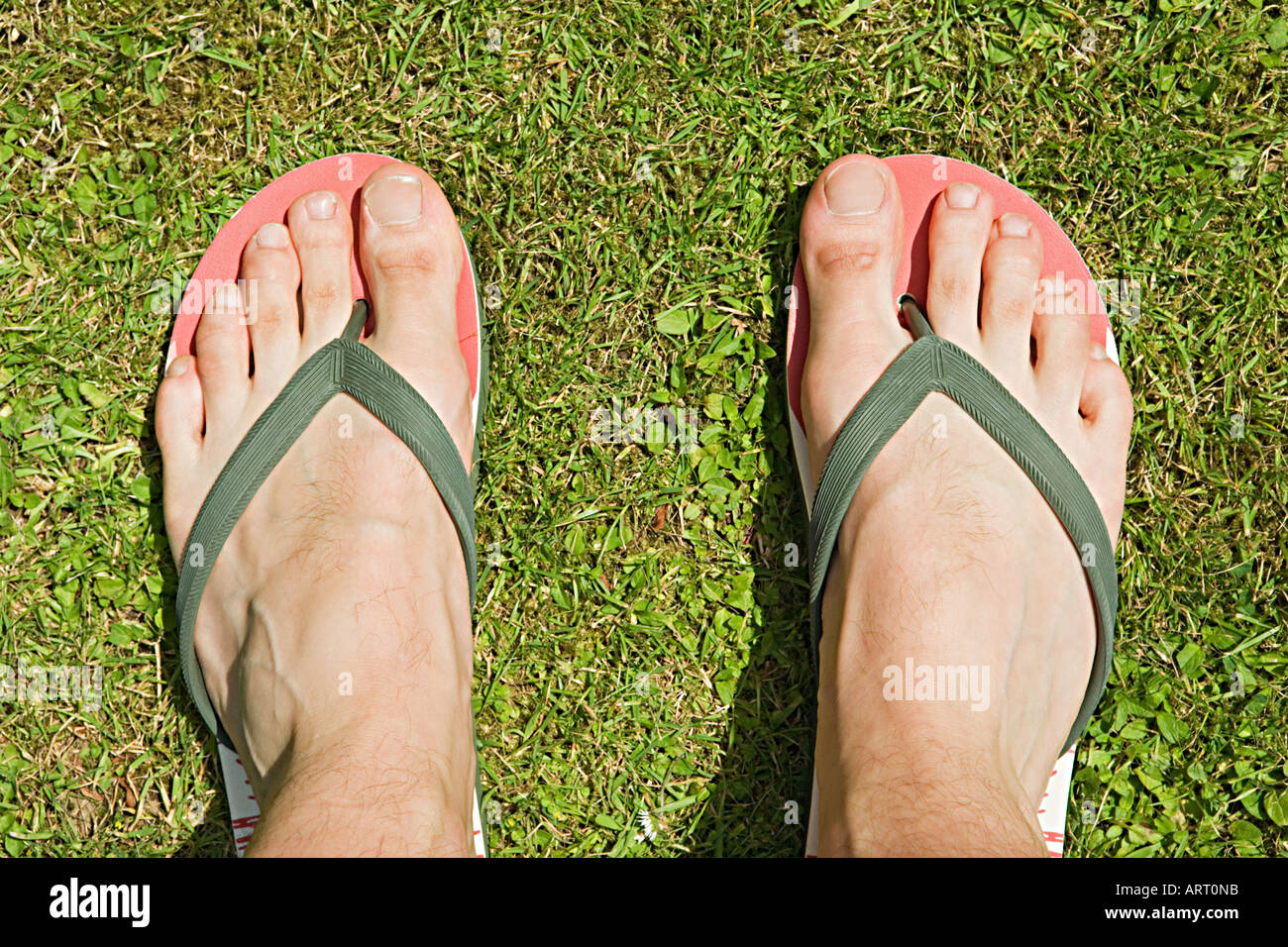Feet of a man in flip flops - Stock Image