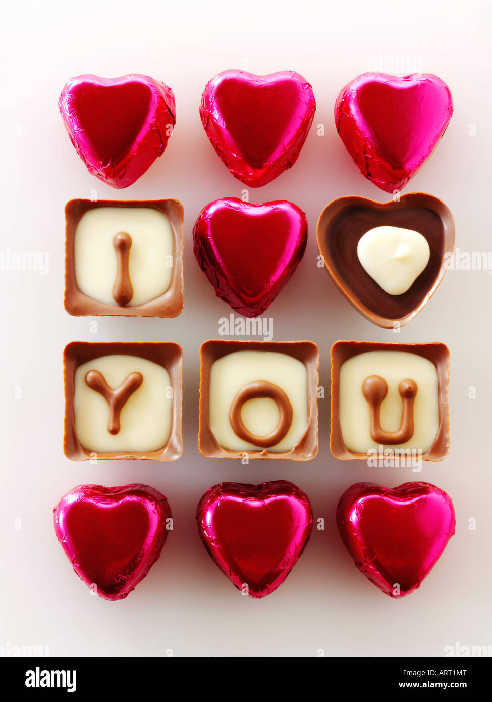 I Love You written in chocolates with red heart shaped chocolates.