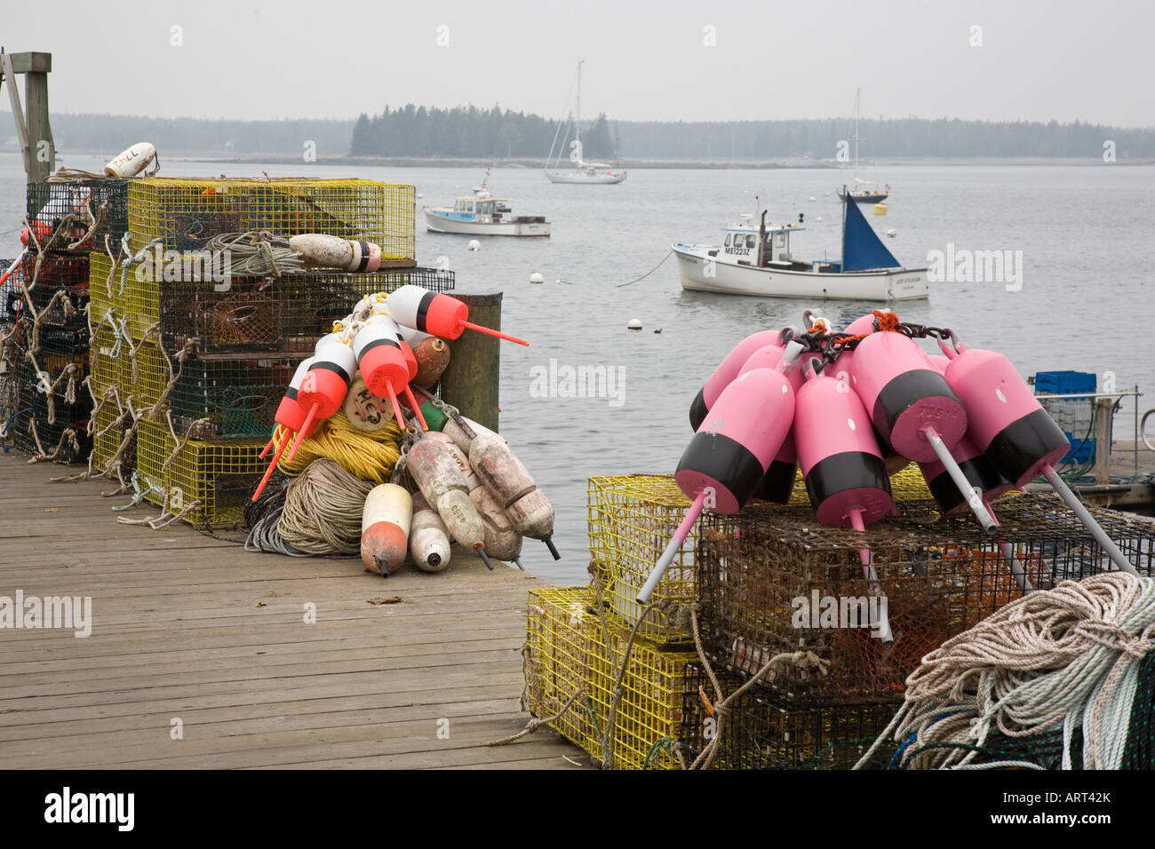 Lobster pots with brightly coloured buoys sit on the dock on a foggy day at Little Cranberry,Maine, USA. Stock Photo