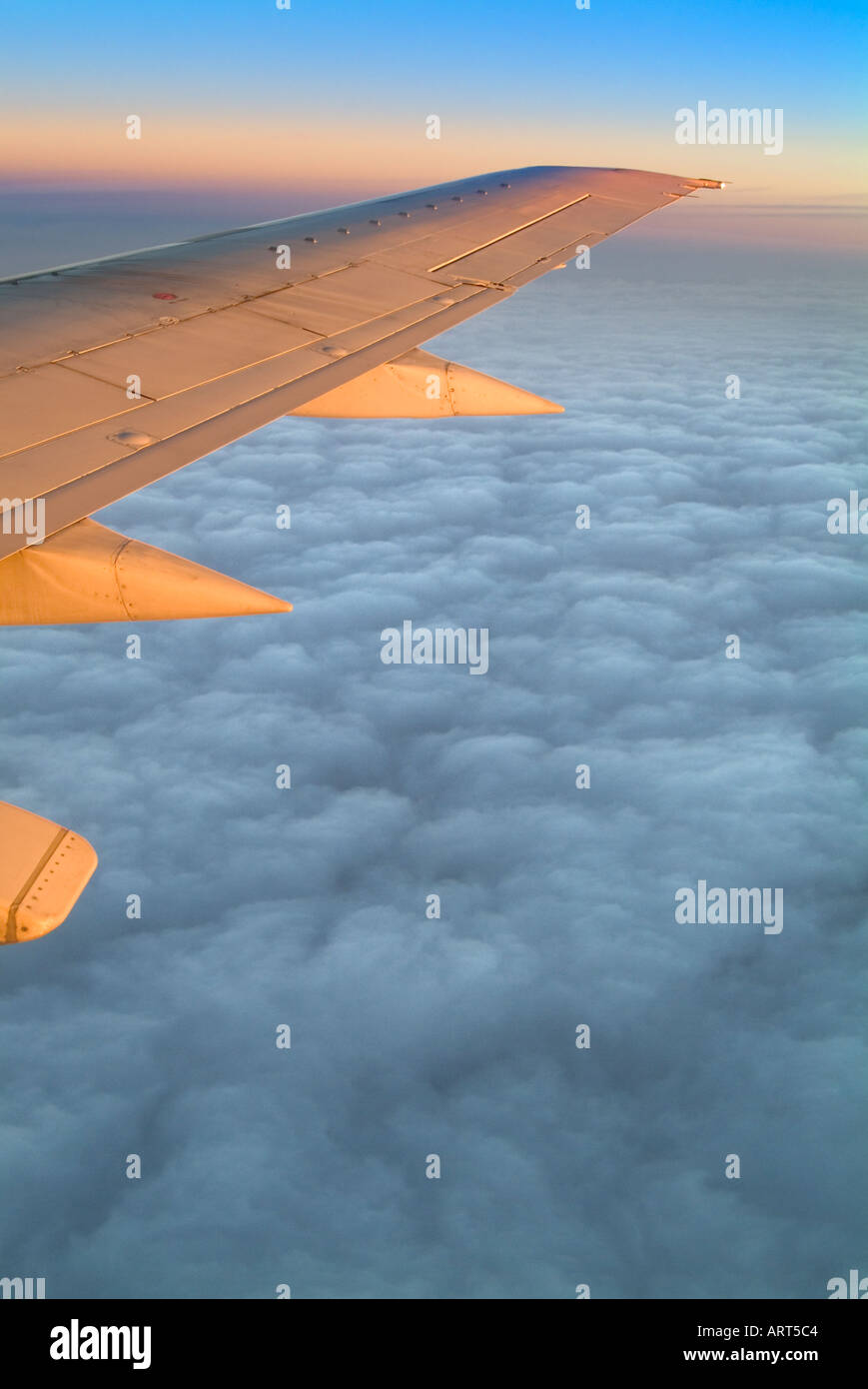 Airplane Jet Wing Flying Above The Clouds At Sunise - Stock Image
