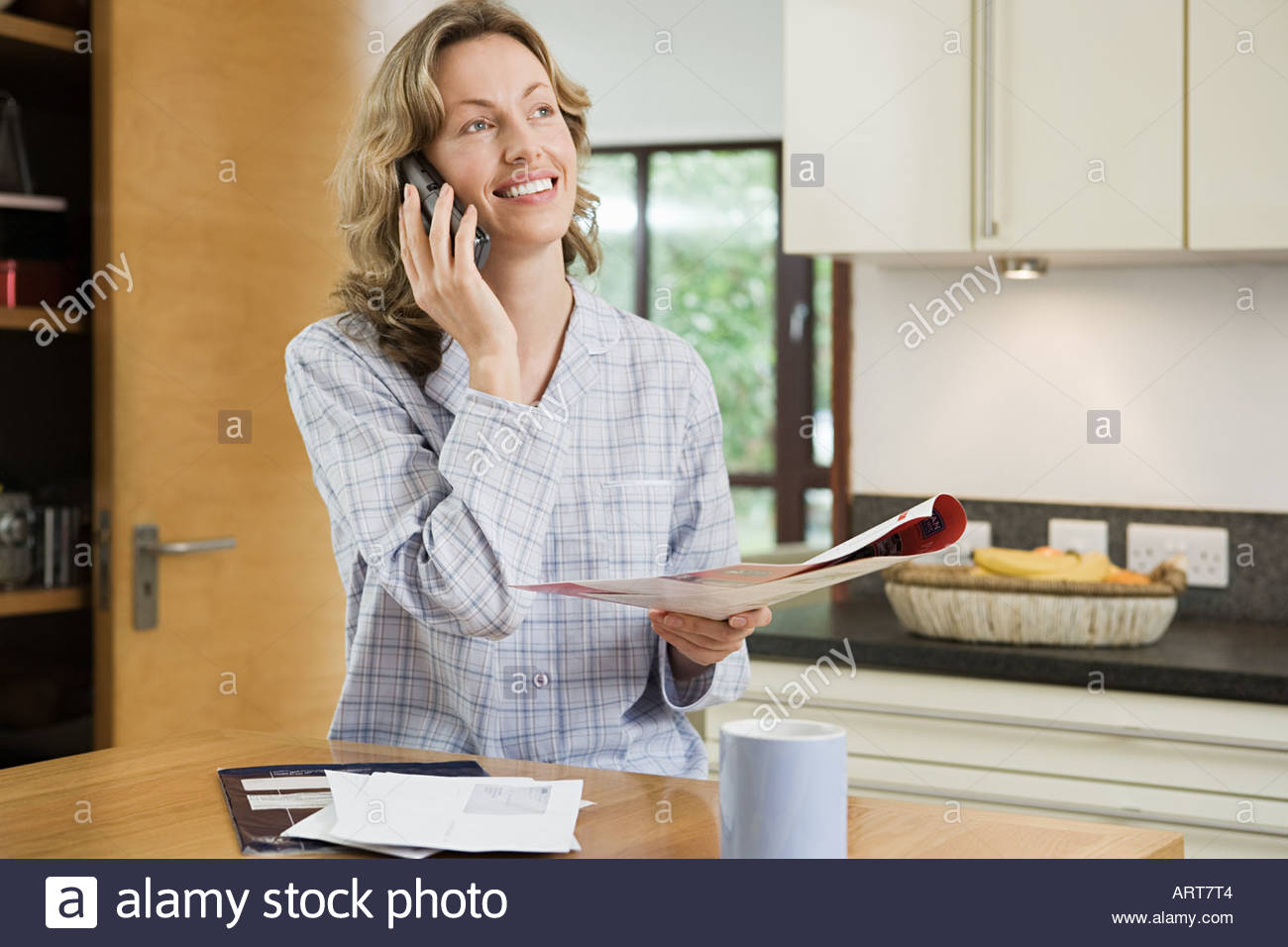 Woman using a cellular telephone in kitchen - Stock Image