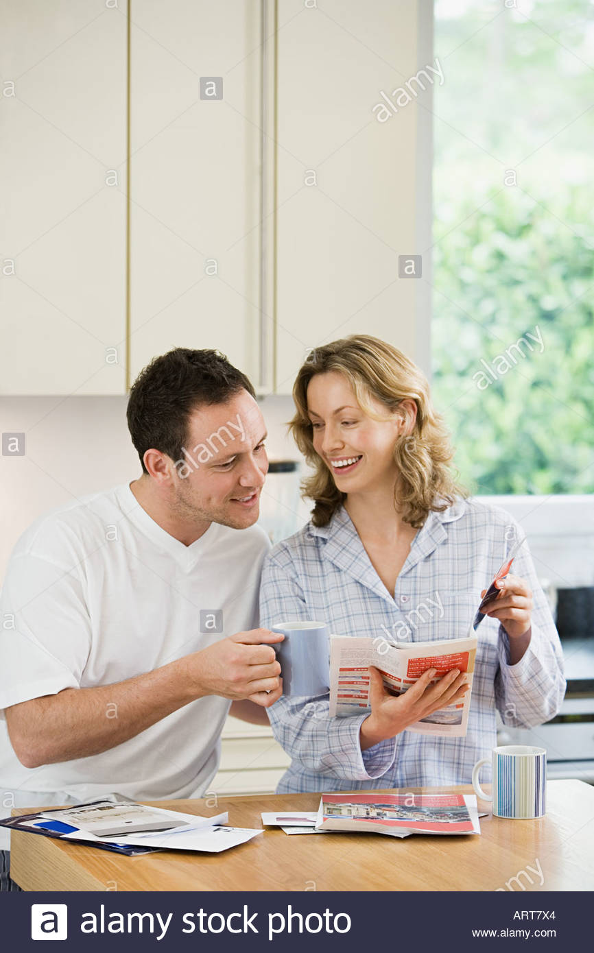 Couple looking at brochure in kitchen - Stock Image