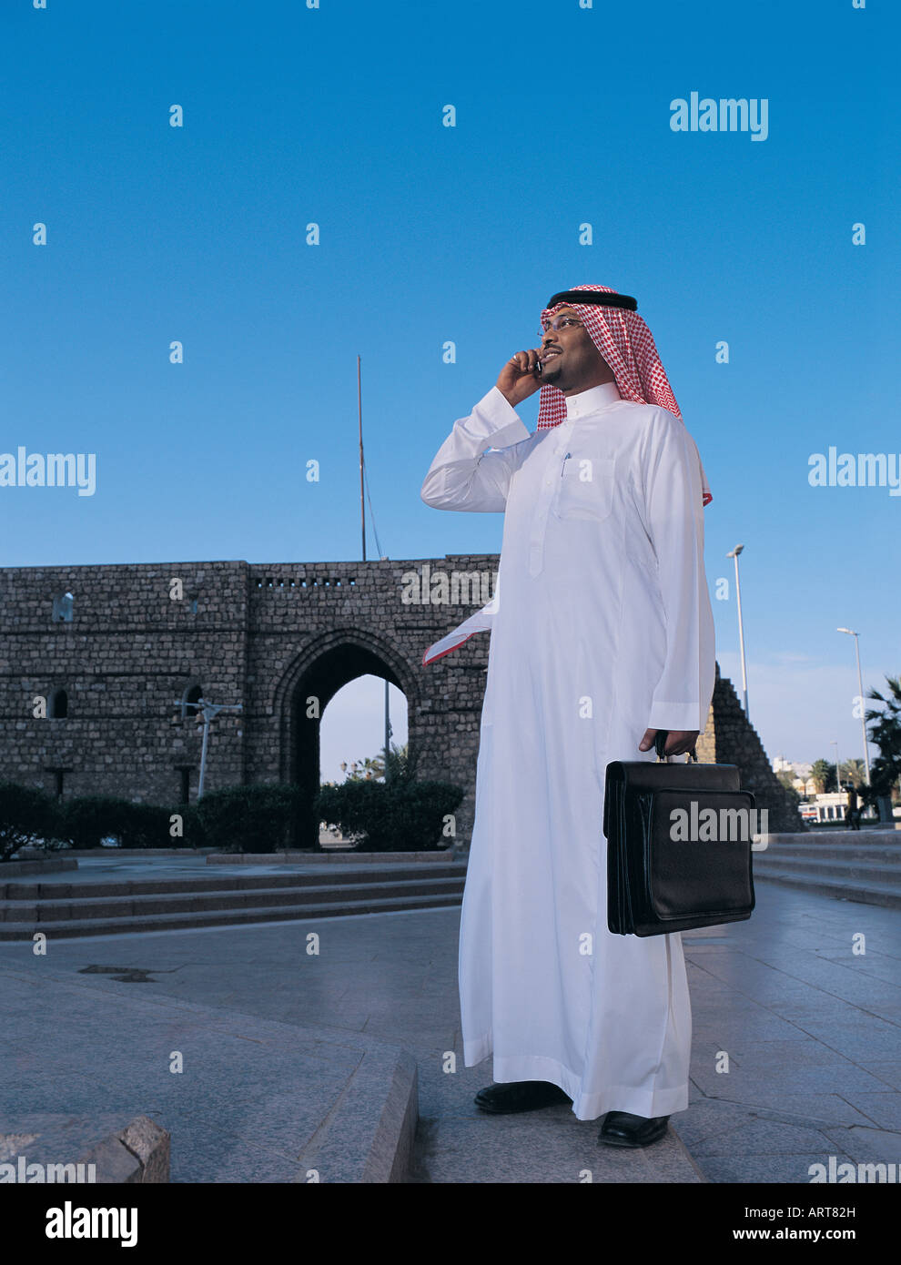 Saudi man using mobile phone near ancient gate of Old Town