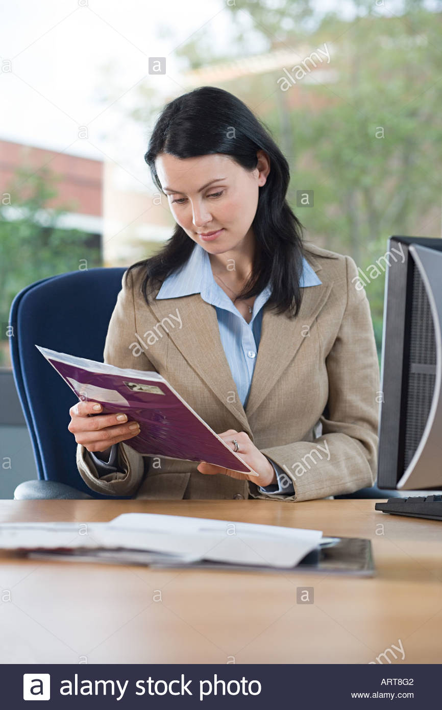 Businesswoman with post at desk - Stock Image
