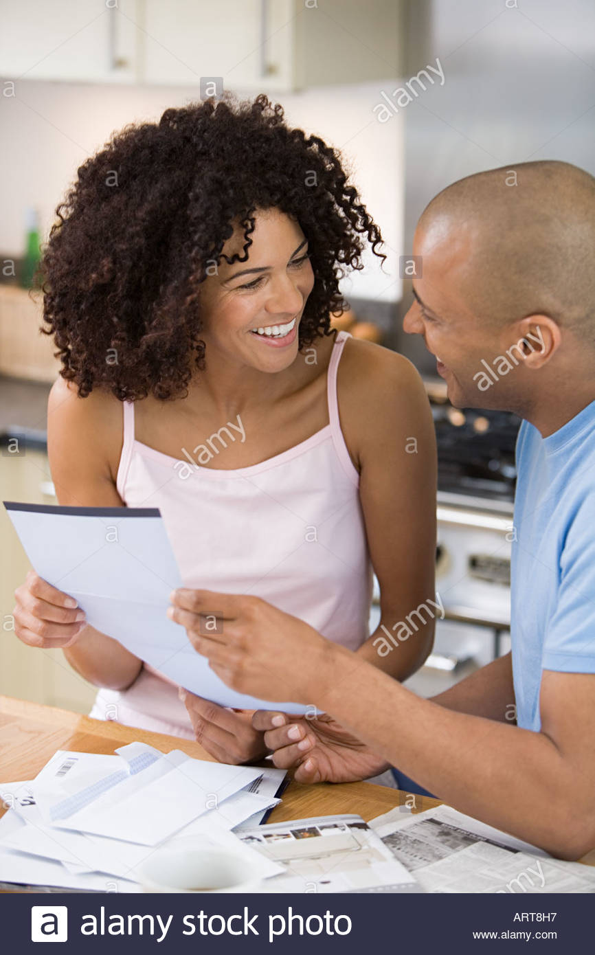 Couple reading post in kitchen - Stock Image