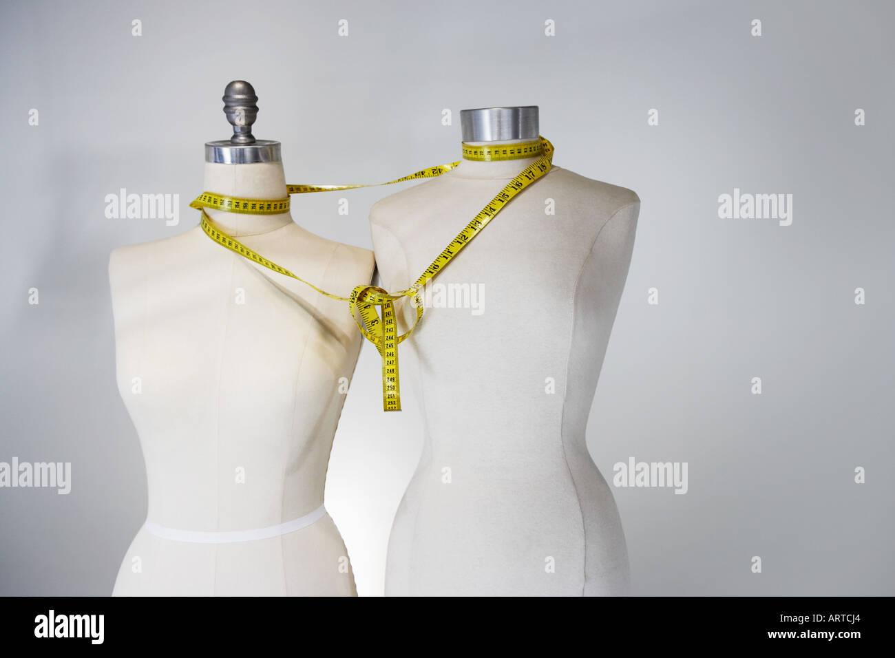 Tape measure tied around tailors dummies - Stock Image