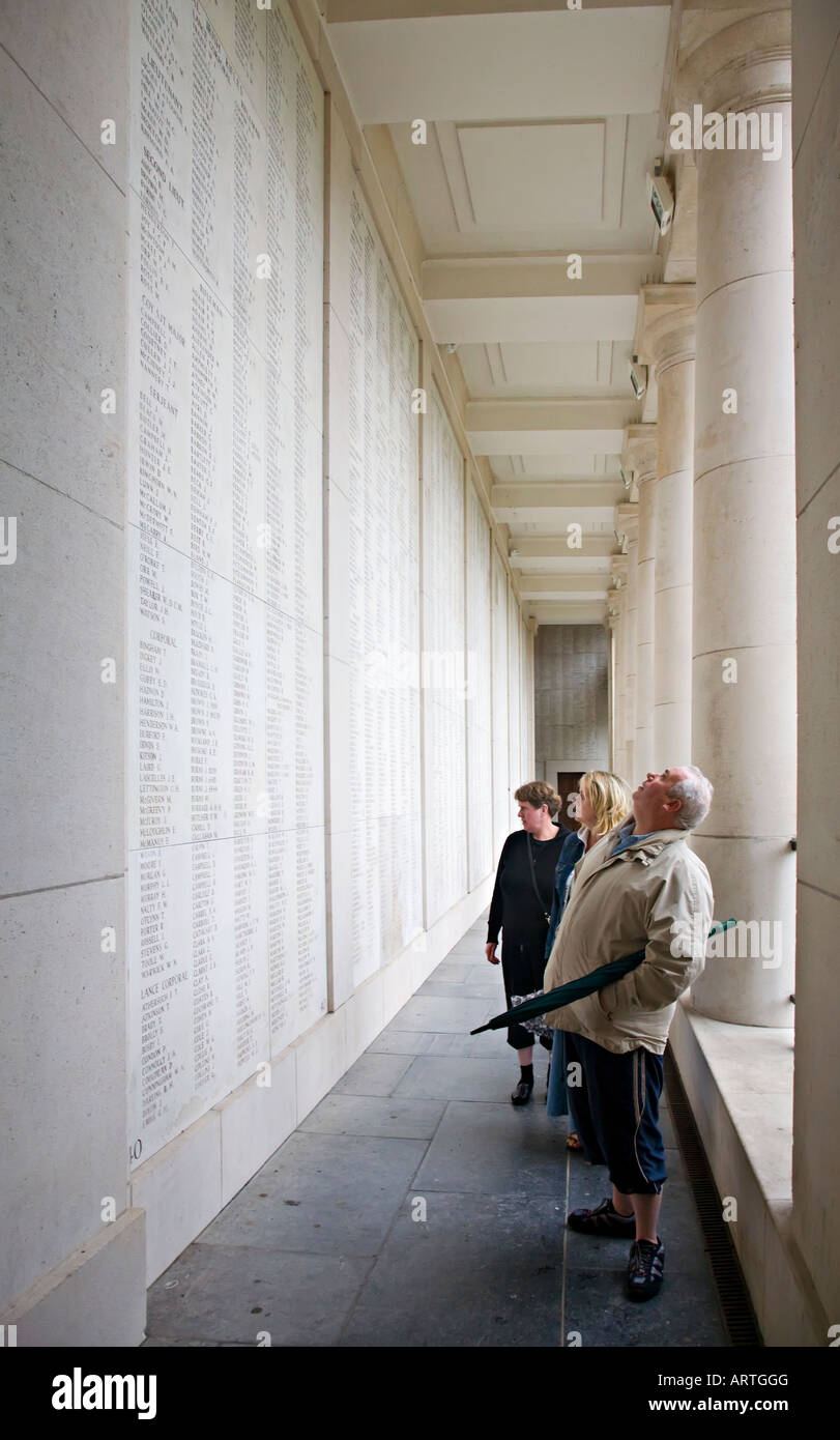 People reading names of war dead inscribed in the Menin Gate Ypres Belgium - Stock Image