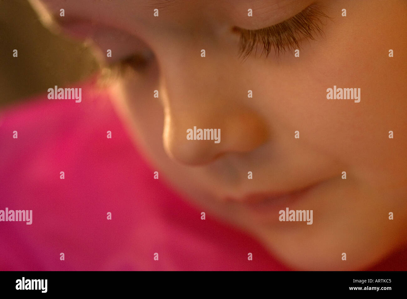 Close up of a young caucasian girl's face contemplating and looking angelic - Stock Image