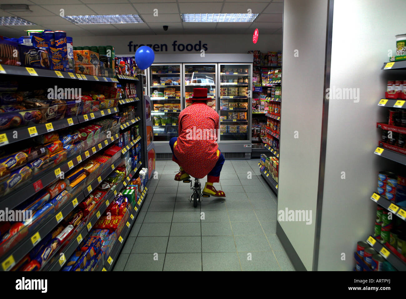 A clown cycles through a shopping aisle on his trick bike in a convenience store in the UK. - Stock Image
