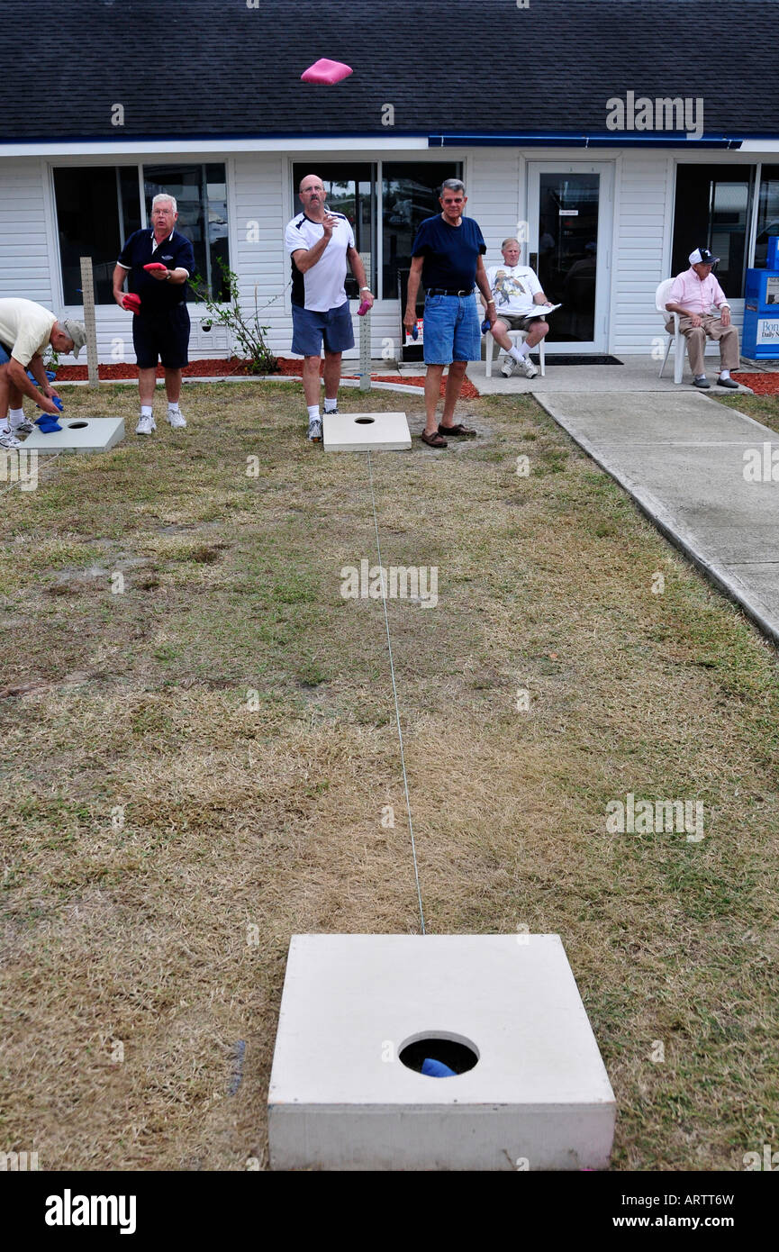 Senior retired citizens play game of bean bag toss in a recreational vehicle camping park in Bonita Springs Florida - Stock Image