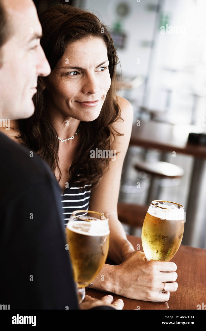 Mid adult couple sitting in a bar and holding beer in stem glasses - Stock Image