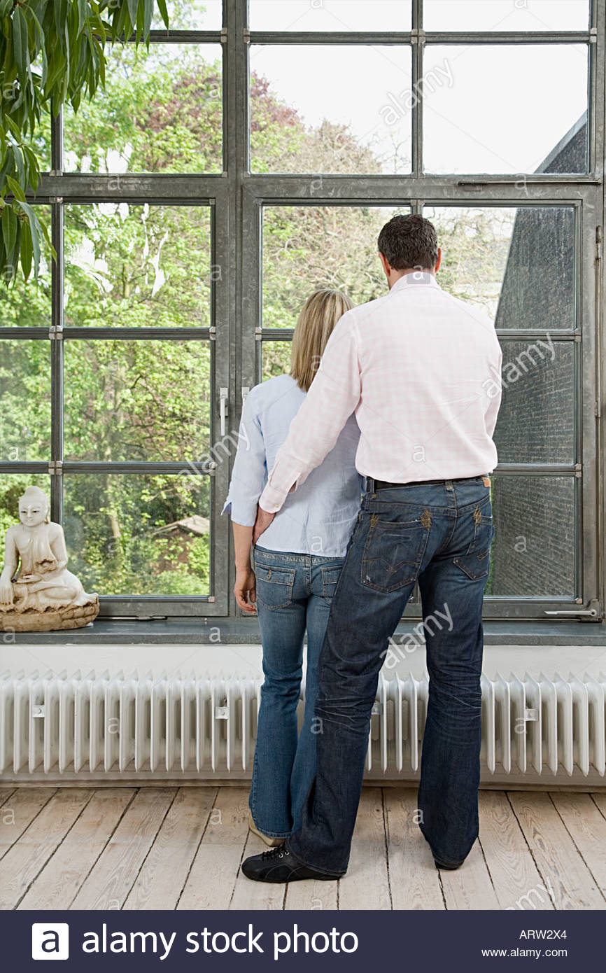 Couple looking out of window - Stock Image