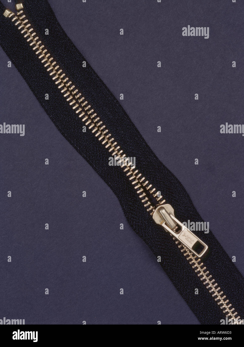 Brass zipper against black background - Stock Image