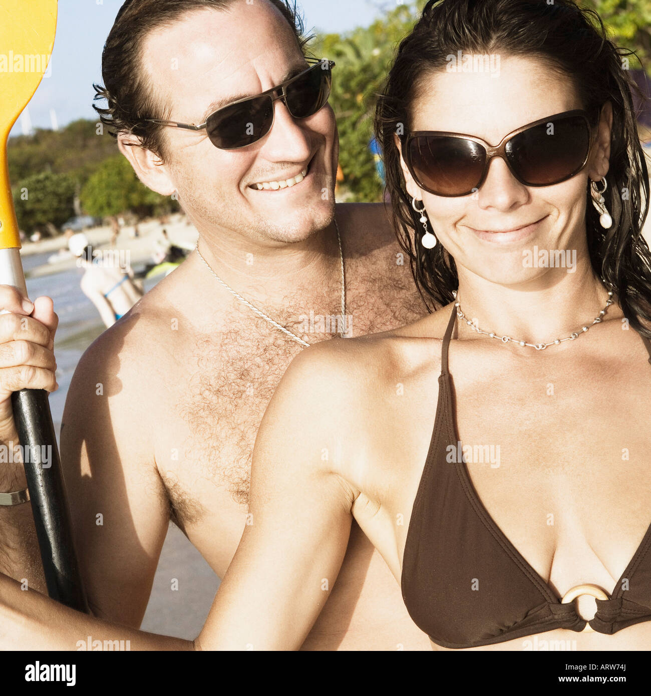 Close-up of a mid adult couple holding oars on the beach - Stock Image