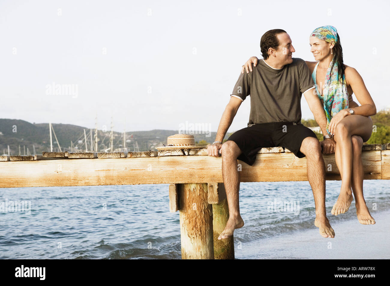 Mid adult woman with her arm around a mid adult man sitting on a jetty - Stock Image
