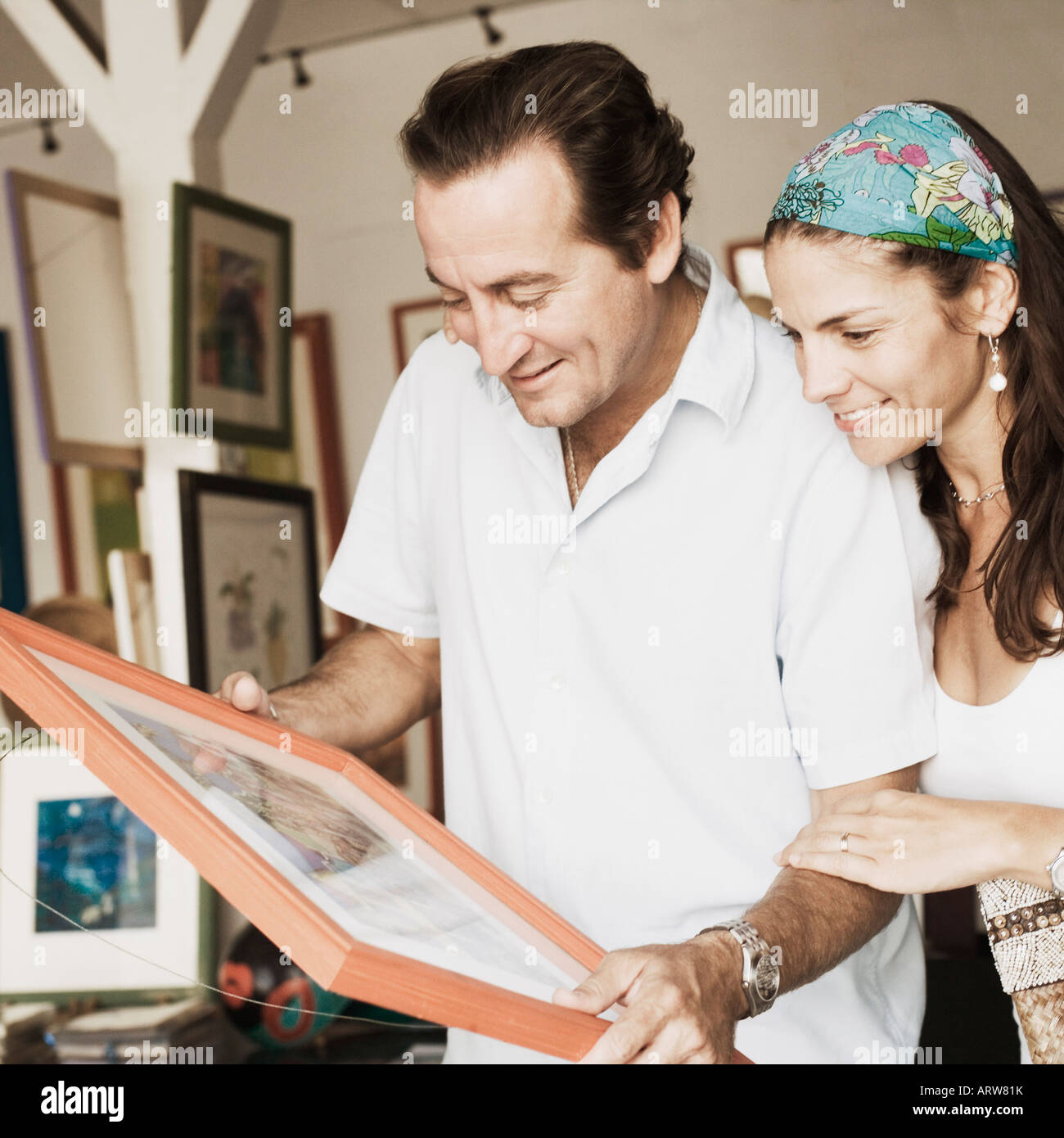 Mid adult couple purchasing paintings from a store - Stock Image