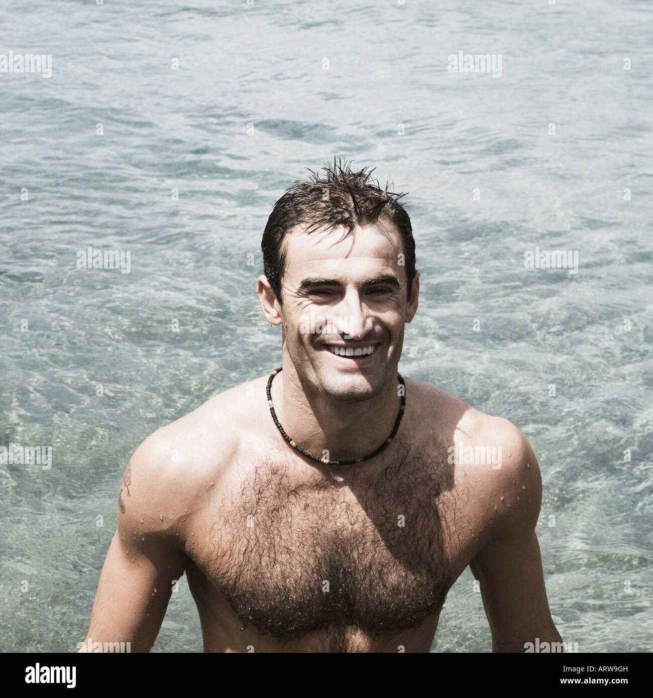 High angle view of a mid adult man standing in a river and smiling - Stock Image