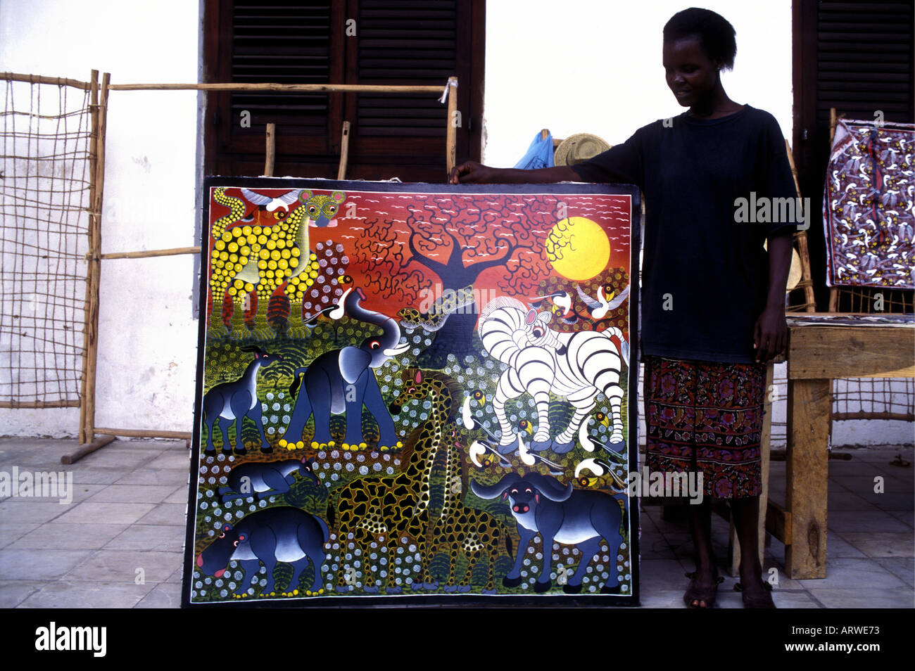 A shopkeeper showing an acrylic painting by a local artist in the stone town Zanzibar Tanzania East Africa - Stock Image