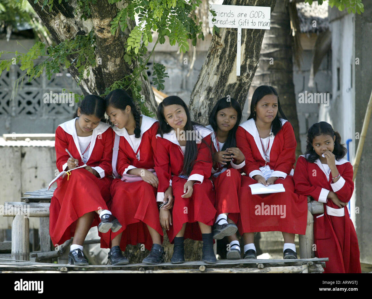 Young Filipinas take a break in the school yard of a Montessori school in Mansalay, Oriental Mindoro, Philippines. - Stock Image