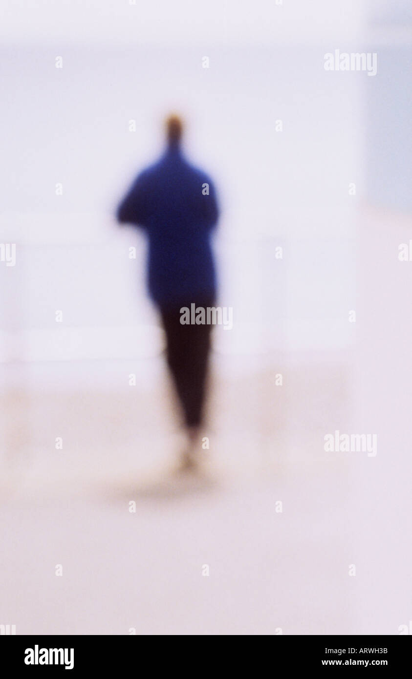 Back view of impressionistic solitary figure leaning on railings and gazing out to distant sea or lake or sky - Stock Image