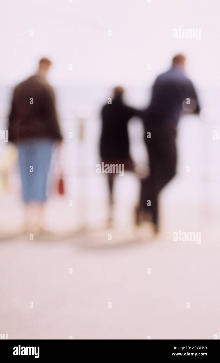 Impressionistic family members at seaside railings with father leaning teenage son sitting and mother holding bags - Stock Image