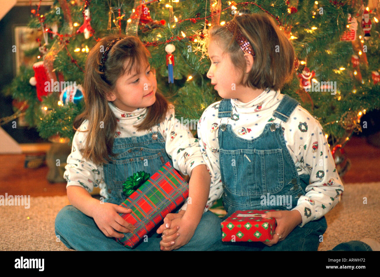Sisters in bib overalls age 8 and 6 holding wrapped Christmas gifts ...