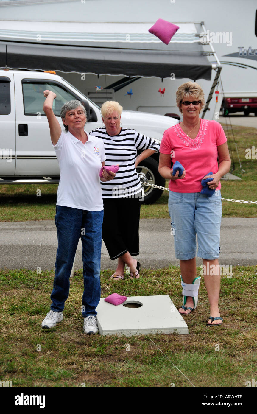 Female Senior retired citizens play game of bean bag toss in a recreational vechile camping park in Bonita Springs - Stock Image