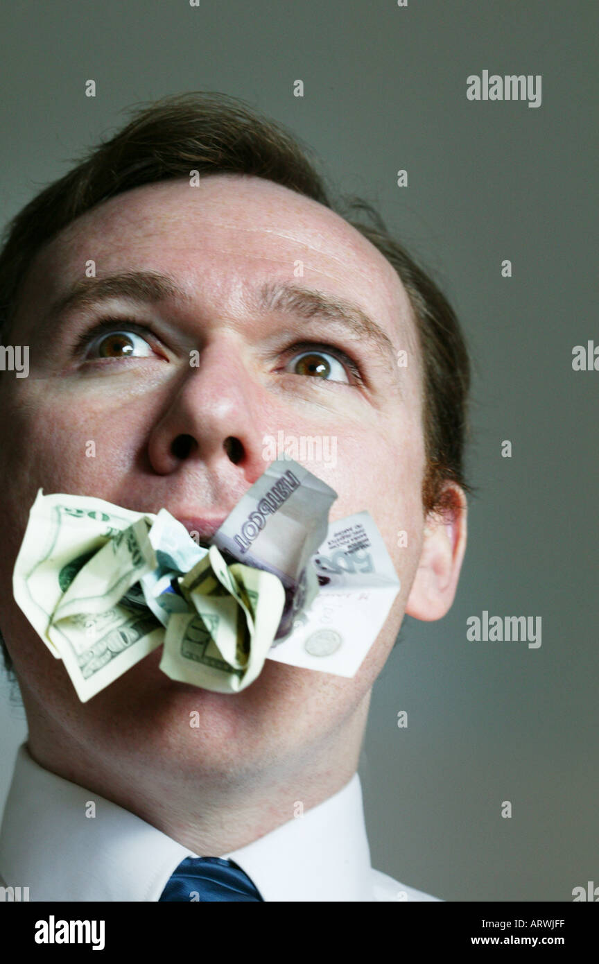 Man with money stuffed in his mouth - Stock Image