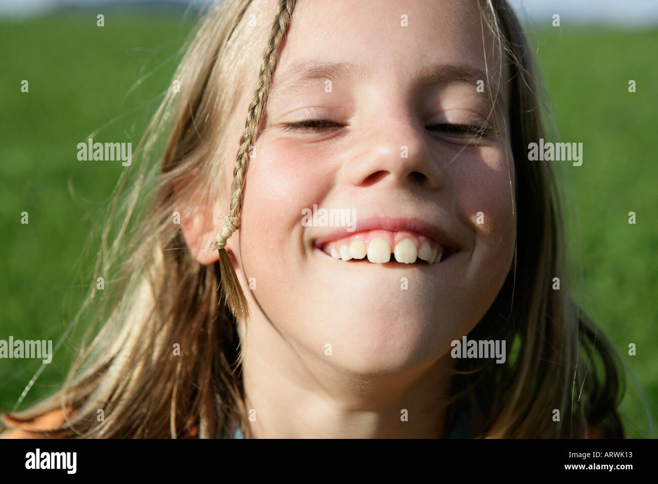Young blonde girls showing her teeth - Stock Image