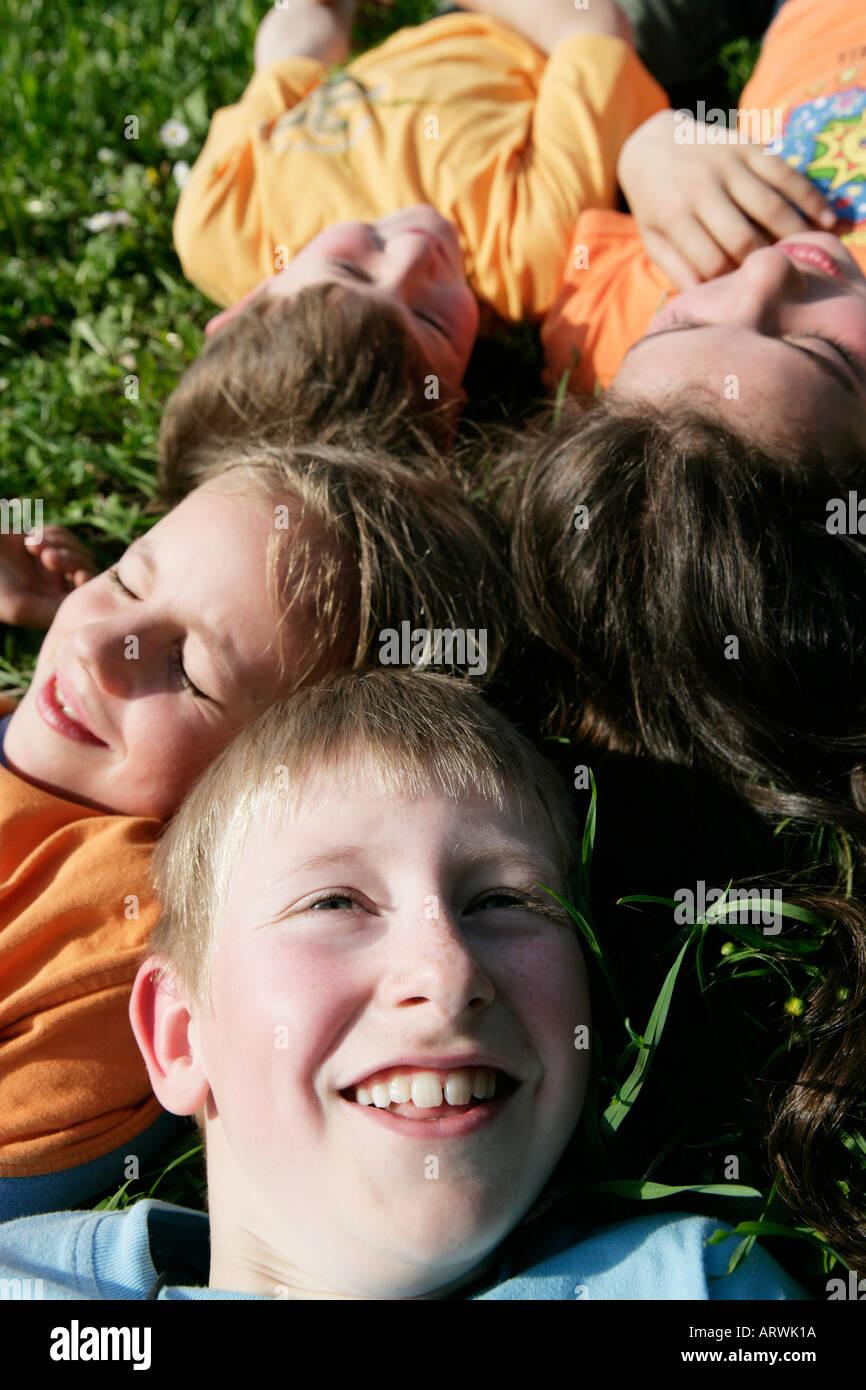 Four children lying head to head - Stock Image