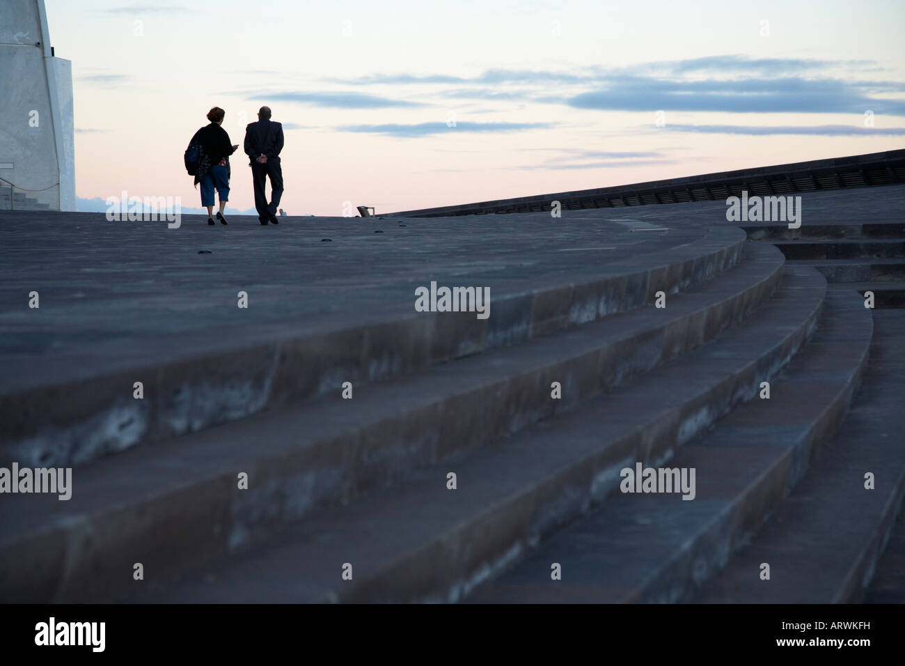single lone female with security guard walking away from steps on with man in the distance in santa cruz tenerife - Stock Image
