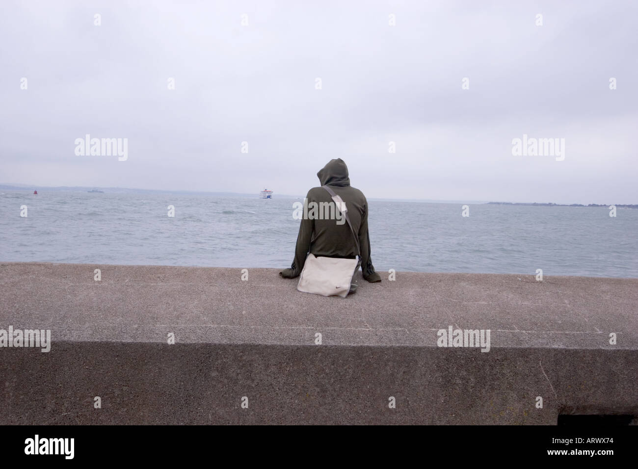 Lone man in hoody hooded top looking out to sea seated on concrete sea defences - Stock Image