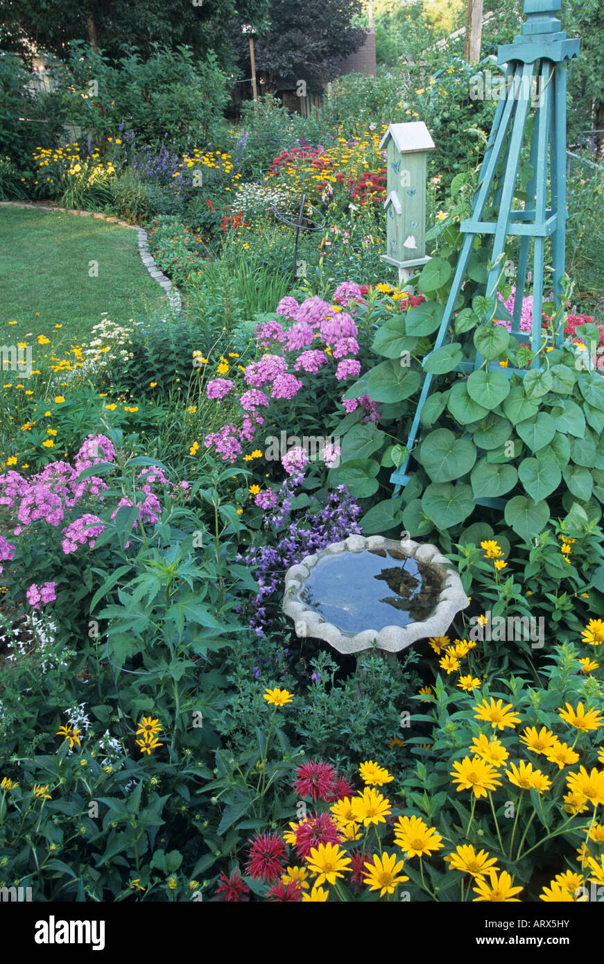 BIRDBATH, TRELLIS AND BUTTERFLY HOUSE IN MINNESOTA GARDEN PLANTED TO  ATTRACT BIRDS AND BUTTERFLIES. JULY.