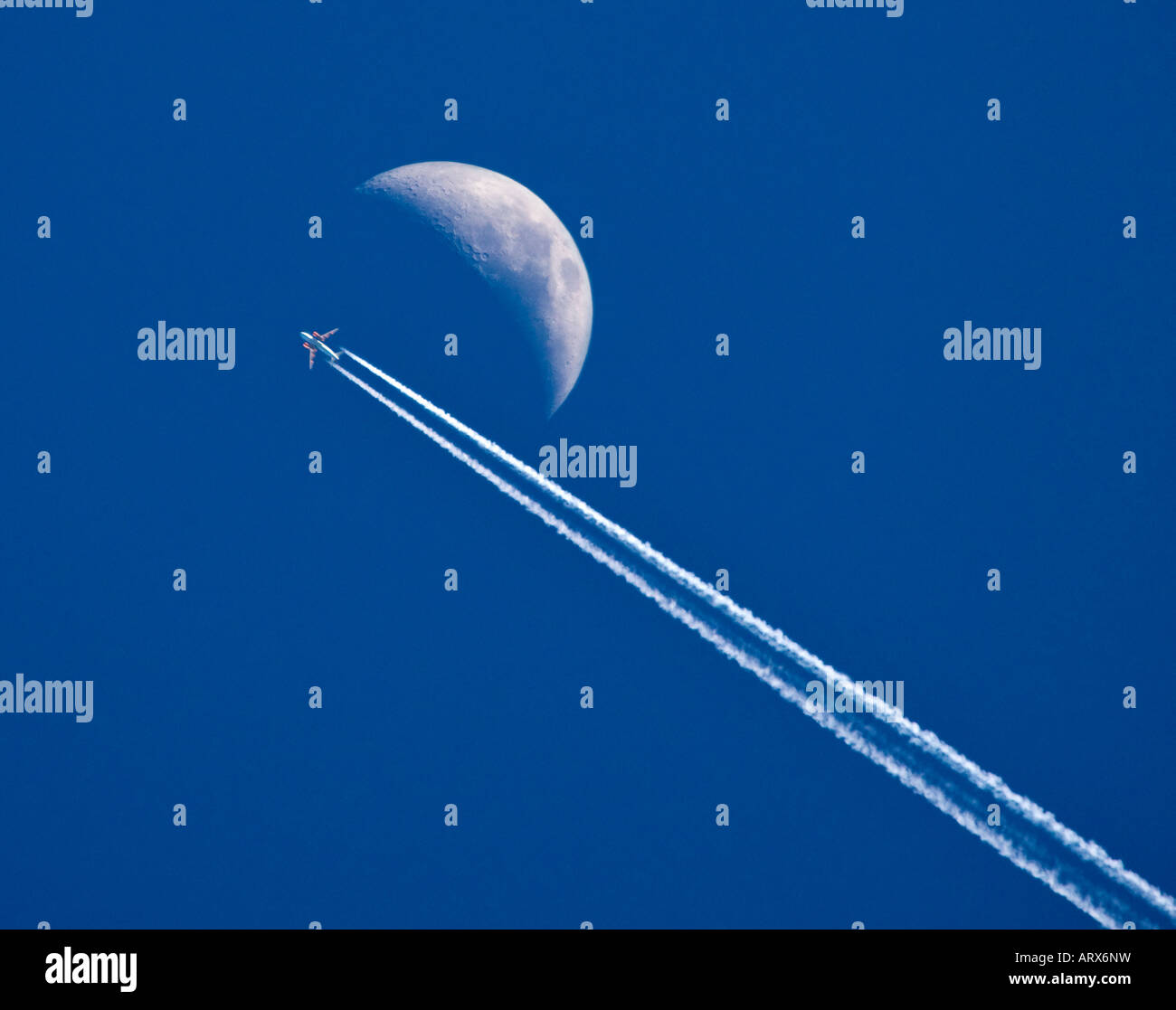 Jet airliner flying past the moon - Stock Image