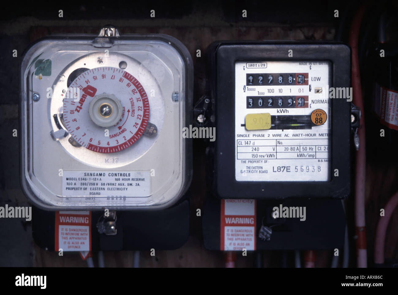 Clock used to stop and start economy time slots for recording off peak readings on adjacent domestic electricity meter - Stock Image