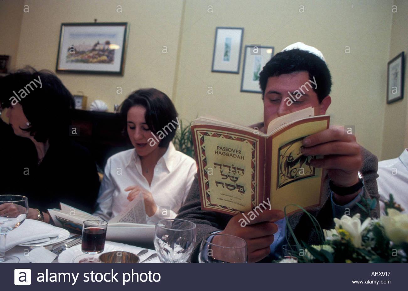 Reading from Hagaddah Passover prayer book at Seder night meal UK - Stock Image